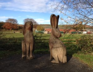 Wood-carved rabbit sculptures in a country park